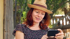La mujer se sienta en el jardín que goza de su smartphone en el sol almacen de metraje de vídeo