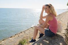 La mujer se sienta en el mar de la orilla imagen de archivo