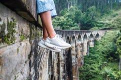 La mujer se sienta en el puente de los arcos de Demodara nueve en Ella, Sri Lanka Foto de archivo