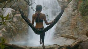 La mujer se sienta en la hamaca suspendida en ramas de árbol