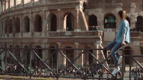 La mujer se sienta en la cerca que mira Colosseum en Roma, Italia y balanceando sus piernas Muchedumbre cerca de la vista Cámara  almacen de video