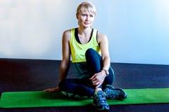 La mujer se sienta en la estera en el gimnasio Fotos de archivo
