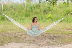 La mujer se sienta en la hamaca en el parque Fotografía de archivo