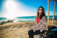 La mujer se sienta en la playa Foto de archivo libre de regalías