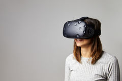 La mujer se sienta en las auriculares de la realidad de Sofa At Home Wearing Virtual foto de archivo