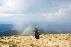 La mujer se sienta en las montañas Imágenes de archivo libres de regalías