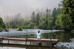 La mujer se sienta en pasarela de madera simple Fotos de archivo libres de regalías