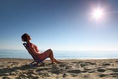 La mujer se sienta en silla en la costa de la persona para asolear Fotografía de archivo