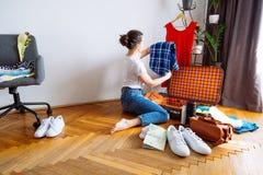La mujer se sienta en suelo ropa del embalaje para el viaje concepto del recorrido Copie el espacio foto de archivo
