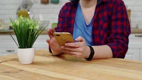 La mujer se sienta en la tabla de cocina y el mensaje de textos en smartphone almacen de metraje de vídeo
