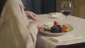 La mujer se sienta en la tabla en el restaurante y come el pedazo grande de carne de la ternera con maíz y de cucchini, bebida fe almacen de metraje de vídeo