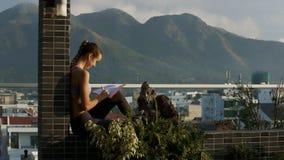 La mujer se sienta en terraza anota pensamientos en diario