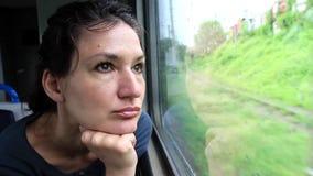 La mujer se sienta en tren cerca de ventana durante el movimiento almacen de metraje de vídeo