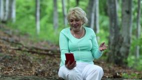 La mujer se sienta en un árbol caido en el bosque y comunica vía su smartphone almacen de metraje de vídeo