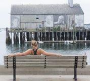 La mujer se sienta en un banco en el puerto de Provincetown Foto de archivo libre de regalías