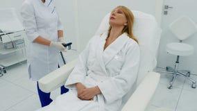 La mujer se sienta en una silla de la cosmetología almacen de metraje de vídeo
