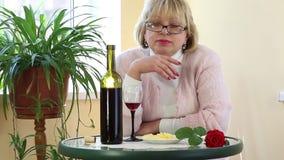La mujer se sienta en una tabla y la mirada en cámara almacen de metraje de vídeo