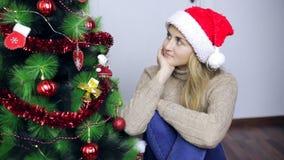 La mujer se sienta por el árbol de navidad y piensa metrajes