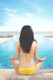 La mujer se sienta y meditación cerca de piscina Foto de archivo libre de regalías