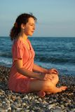 La mujer se sienta y meditación en tierra del mar Imagen de archivo