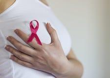 La mujer se sostiene el pecho y tiene muestra para el cáncer de pecho en él fotos de archivo libres de regalías