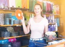 La mujer se sostiene en sus objetos de las manos para la cocina Foto de archivo libre de regalías