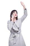 La mujer se vistió en hablar que agitaba de la capa gris en el teléfono Foto de archivo
