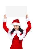 La mujer se vistió en Papá Noel con la tarjeta en blanco Foto de archivo