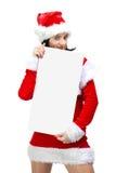 La mujer se vistió en Papá Noel con la tarjeta en blanco Imagen de archivo libre de regalías