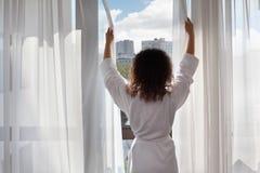La mujer se vistió en soportes de la albornoz cerca de ventana Foto de archivo libre de regalías