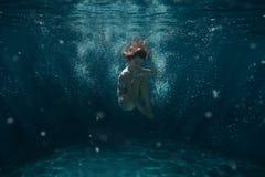 La mujer se zambulle bajo el agua Foto de archivo