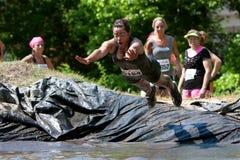 La mujer se zambulle en hueco del fango en curso de obstáculo Foto de archivo