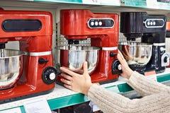 La mujer selecciona el procesador de alimentos eléctrico Fotos de archivo libres de regalías