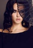 La mujer sensual hermosa con el pelo oscuro que sostiene el cordón negro aviva a disposición Imagen de archivo