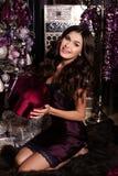 La mujer sensual hermosa lleva el vestido elegante, presentando al lado del árbol de navidad imagenes de archivo