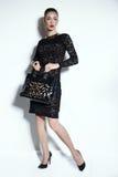 La mujer sensual magnífica con el peinado elegante, lleva el vestido del cordón y la joya negros Foto de archivo libre de regalías