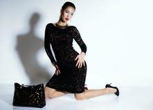 La mujer sensual magnífica con el peinado elegante, lleva el vestido del cordón y la joya negros Fotos de archivo libres de regalías