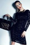 La mujer sensual magnífica con el peinado elegante, lleva el vestido del cordón y la joya negros Imagen de archivo