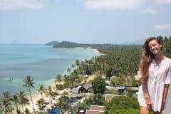 La mujer sensual muy elegante de los jóvenes que presenta en la playa tropical asombrosa con el océano azul disfruta de su día de Imagen de archivo libre de regalías