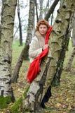 La mujer seria con los costes de una bufanda del rojo que se inclinan contra un abedul en la madera Fotos de archivo