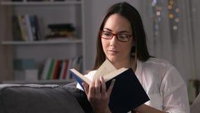 La mujer seria lee un libro en la noche metrajes