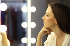 La mujer seria que mira compone el espejo Imagen de archivo
