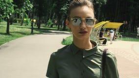 La mujer sexual con los labios rojos en gafas de sol del espejo camina en el parque almacen de video