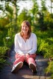 La mujer sienta la sonrisa del parque divertida Fotos de archivo