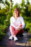 La mujer sienta la sonrisa del parque divertida Foto de archivo libre de regalías