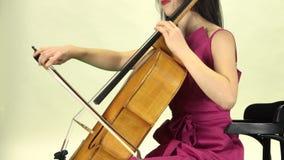 La mujer sienta y toca el violoncelo Vista lateral Fondo blanco almacen de video
