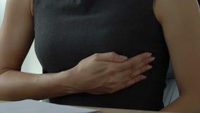 La mujer siente dolor del pecho en el lugar de trabajo, comprobando la glándula mamaria, los síntomas del cáncer almacen de video