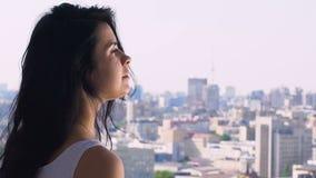 La mujer siente serenidad y calma en ciudad en el fondo, scape urbano de la paz de la mente metrajes