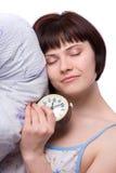 La mujer soñolienta es durmiente y que sostiene el reloj de alarma Fotos de archivo libres de regalías