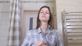 La mujer soñolienta que acaba de despertar con una resaca en el cuarto de baño sujeta su camisa y se pone en orden almacen de metraje de vídeo